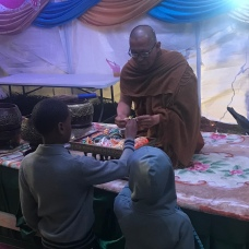 A monk giving us bracelets.